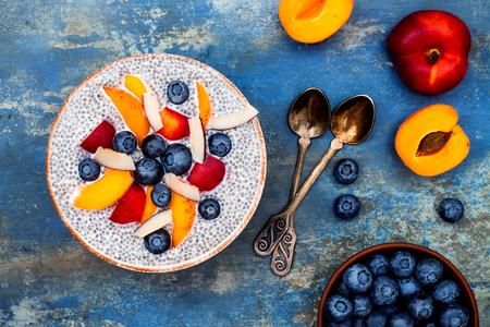 デトックスと健康的なスーパー フード朝食ボウル コンセプト。ビーガン ココナッツ ミルク嘉種子プディング様々 なフルーツとブルーベリーの青い