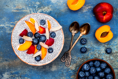 Detox and healthy superfoods breakfast bowl concept. Vegan coconut milk chia seeds pudding over blue stone table with various fruits and blueberries. Overhead, top view, flat lay. Stock fotó