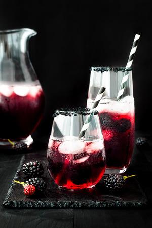 Bevanda Blackberry in bicchieri con orlo di zucchero nero per l'autunno e feste di Halloween Archivio Fotografico - 64117344