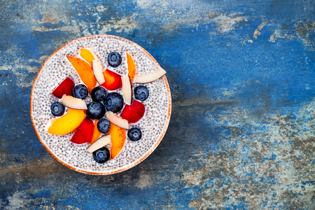 Detox and healthy superfoods breakfast bowl concept. Vegan coconut milk chia seeds pudding over blue stone table with various fruits and blueberries. Overhead, top view, flat lay. Banque d'images