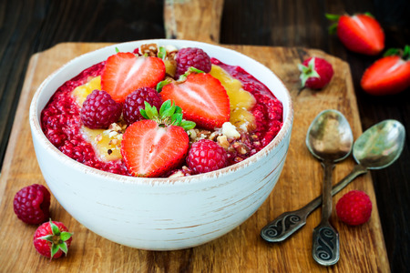 maca: Healthy breakfast. Mango maca smoothie bowl topped with hazelnuts, oat granola, fresh berries and raspberry puree. Rustic style, vintage silverware. Stock Photo