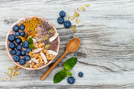 Acai breakfast superfoods smoothies bowl topped with chia, flax and pumpkin seeds, bee pollen, granola, coconut flakes and blueberries. Overhead, top view, flat lay Stockfoto