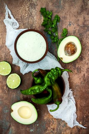 crema: Preparing avocado cilantro sauce for fish tacos. Lime crema in a bowl on vintage stone background. Recipe for Cinco de Mayo party. Top view.