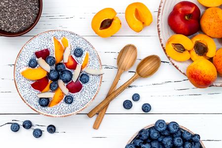 Detox en gezonde superfoods ontbijt kom concept. Vegan kokosmelk chia zaden pudding op rustieke tafel met verschillende vruchten en bosbessen. Overhead, bovenaanzicht, plat. Stockfoto