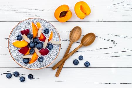 Desintoxicación y saludable súper alimentos desayuno tazón concepto. Vegan leche de coco chia semillas budín sobre mesa rústica con diversas frutas y arándanos. Detrás, vista superior, plano.