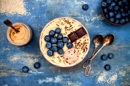 Gluten free amaranth and quinoa porridge breakfast bowl with blueberries and chocolate over vintage blue background. Top view, overhead, flat lay. Copy space 스톡 콘텐츠