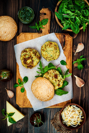 vegetarian hamburger: Zucchini quinoa veggie burger with pesto sauce and sprouts. Vegetarian burger on a cooking sheet ready to prepare hamburger. Top view, overhead, flat lay