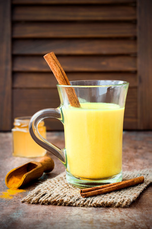 Turmeric golden milk latte with cinnamon sticks and honey. Detox liver fat burner, immune boosting, anti inflammatory healthy cozy drink
