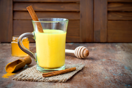 Turmeric golden milk latte with cinnamon sticks and honey. Detox liver fat burner, immune boosting, anti inflammatory healthy cozy drink. Copy space