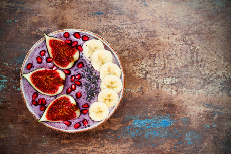 Healthy fall and winter breakfast set. Acai superfoods smoothies bowl with chia seeds, pomegranate, sliced banana, fresh figs and hazelnut butter. Overhead, top view. Copy space