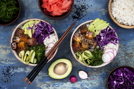 Hawaiian tuna poke bowl with seaweed, avocado, red cabbage slaw, radishes and black sesame seeds. Top view, overhead, flat lay