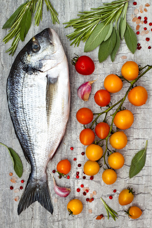 Fresh uncooked dorado or sea bream fish with lemon, aromatic herbs, vegetables and spices over grey stone background. Top view