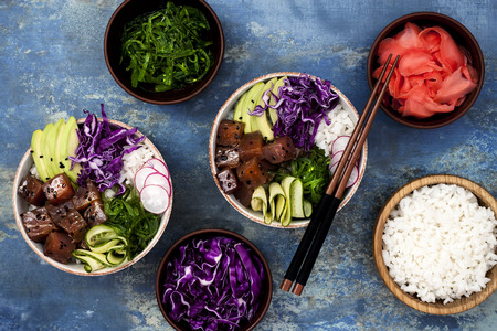 poke: Hawaiian tuna poke bowl with seaweed, avocado, red cabbage slaw, radishes and black sesame seeds. Top view, overhead, flat lay