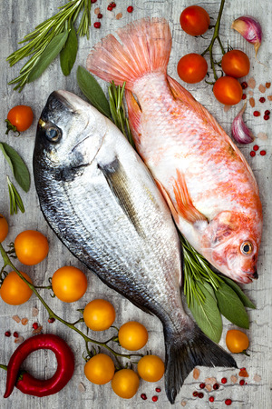 Fresh uncooked dorado or sea bream and red tilapia fish with lemon, aromatic herbs, vegetables and spices over grey stone background. Top view