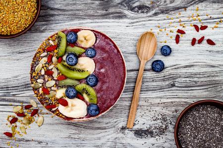 Acai śniadaniowe superfoods smoothie miseczka z nasionami chia, pyłkiem pszczeli, dodatkami jagodowymi goji i owocami. Widok ogólny, widok z góry, płaski układ, kopia