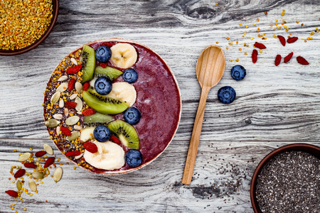 Acai breakfast superfoods smoothies bowl with chia seeds, bee pollen, goji berry toppings and fruits. Overhead, top view, flat lay, copy space
