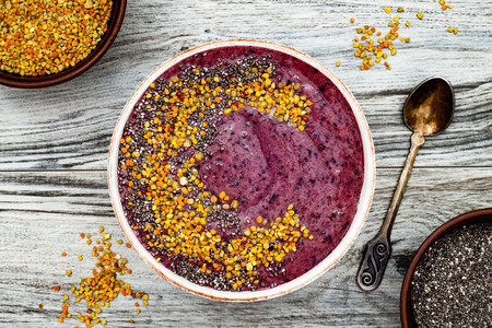 maca: Acai breakfast superfoods smoothies bowl with chia seeds, bee pollen toppings. Immune boosting, anti inflammatory smoothie with turmeric, honey and maca powder. Overhead, top view, flat lay, copy space Stock Photo