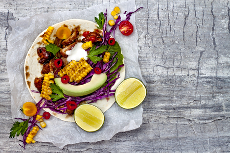 Mexican tacos with avocado, slow cooked meat, grilled corn, red cabbage slaw and chili salsa on rustic stone table. Recipe for Cinco de Mayo party. Top view. Copy space background
