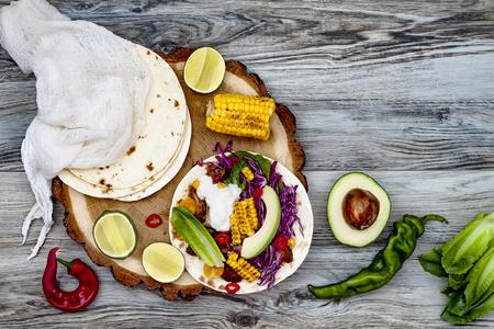 tortilla de maiz: Tacos mexicanos con aguacate, carne cocida lenta, maíz a la parrilla, repollo de col roja y salsa de chile en la mesa de piedra rústica. Receta para la fiesta del Cinco de Mayo. Vista superior. Copiar el espacio de fondo