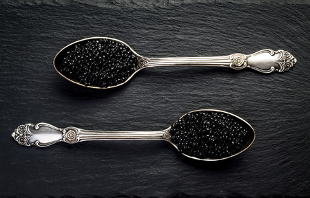 Two vintage silver spoons with black sturgeon caviar on black slate stone background. Top view, flat lay, copy space