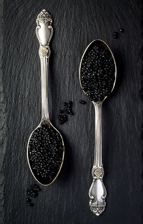 sturgeon: Two vintage silver spoons with black sturgeon caviar on black slate stone background. Top view, flat lay, copy space