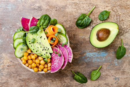 Vegan, detox Buddha bowl recipe with avocado, carrots, spinach, chickpeas and radishes. Top view, flat lay, copy space