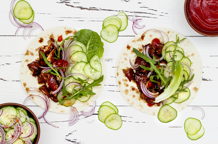 Korean slow cooked beef tacos with asian cucumber slaw and sriracha ketchup. Top view, flat lay, copy space