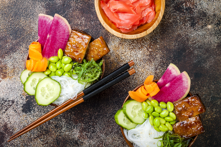 Vegan tofu poke bowls with seaweed, watermelon radish, cucumber, edamame beans and rice noodles. Copy space background, overhead, flat lay