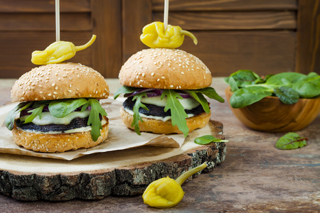 焼きポルトベロ マッシュ ルーム バーガー。健康な野菜玉ねぎ、ルッコラ、チーズ、ピリ辛漬け唐辛子とタルタル ソースのハンバーグスペースの背