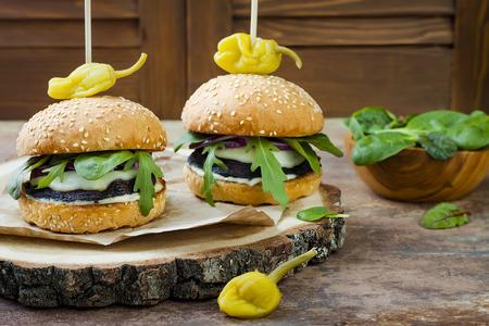 Hamburguesa de hongos portobello a la parrilla. Hamburguesa de vegetales saludables con cebolla, rúcula, queso, pimientos picantes picantes y salsa tártara. Copie el fondo del espacio Foto de archivo - 75481070
