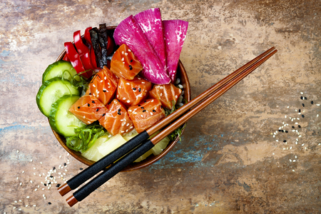 Hawaiian salmon poke bowl with seaweed, watermelon radish, cucumber, pineapple and sesame seeds. Copy space background, overhead, flat lay