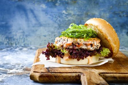 아시아 스타일 연어 햄버거 구운 된 새우, 해 초, 양상추와 매운 sriracha 마요네즈 소스 갈색 종이 소박한 나무 보드에 조각에 재직했습니다. 밝은 파란