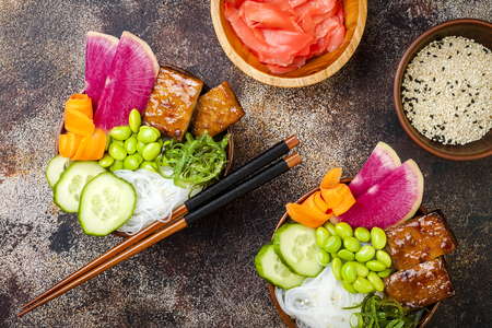 mee: Vegan tofu poke bowls with seaweed, watermelon radish, cucumber, edamame beans and rice noodles. Copy space background, overhead, flat lay