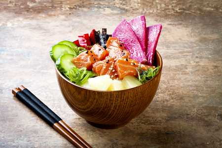 Hawaiian salmon poke bowl with seaweed, watermelon radish, cucumber, pineapple and sesame seeds. Copy space background