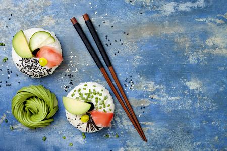 ビーガン寿司ドーナツは紅生姜、アボカド、キュウリ、チャイブ、海苔とゴマと青の背景に設定します。寿司食品雑種傾向。オーバーヘッドのトッ