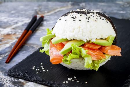 自家製アジアン スタイル グルテン無料寿司鮭バーガー。寿司食品雑種傾向。コピー スペースと明るい青色の背景