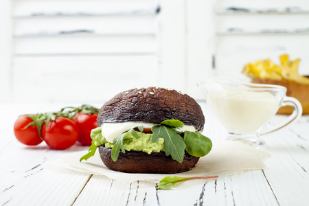 Grilled portobello bun mushroom burger. Vegan, gluten free, grain free, healthy veggies hamburger with guacamole, fresh vegetables, cashew cheese sauce and crispy baked zucchini fries. Copy space Imagens - 75481096