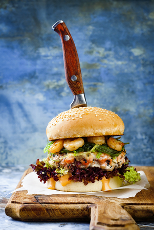 Asian style salmon burger with grilled shrimps, seaweed, lettuce and spicy sriracha mayo sauce served on pieces of brown paper on a rustic wooden board. Bright blue background with copyspace Stock Photo