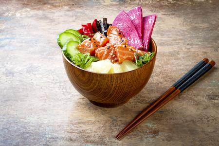 Hawaiian salmon poke bowl with seaweed, watermelon radish, cucumber, pineapple and sesame seeds. Copy space background