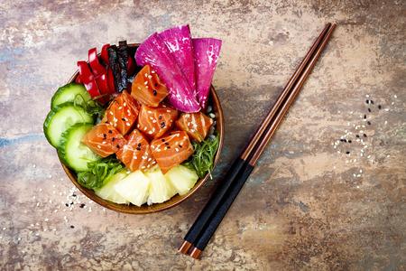 Hawaiiaanse Zalm Poke Bowl Met Zeewier, Watermeloen Radijs, Komkommer, Ananas En Sesamzaden. Kopieer de ruimte achtergrond, overhead, vlakke lay Stockfoto