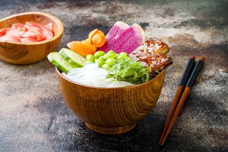 Vegan tofu poke bowls with seaweed, watermelon radish, cucumber, edamame beans and rice noodles. Copy space background