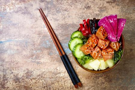 Hawaiian salmon poke bowl with seaweed, watermelon radish, cucumber, pineapple and sesame seeds. Copy space background, overhead, flat lay