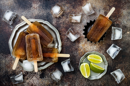 Rum and coke cocktail popsicles with lime juice. Cuba libre homemade frozen alcoholic paletas - ice pops. Overhead, flat lay, top view, copy space