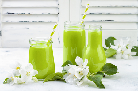 Detox, healthy green smoothie in jars and bottle. White wooden rustic background with apple blossom