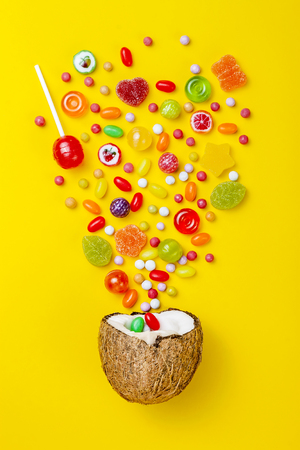 Colorful explosion of candies in coconut on yellow colored background, creative still life, flat lay style Banque d'images