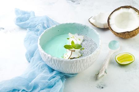 철저한 채식주의 자 파란색 스피루리나 스무디와 치아 푸딩 그릇에 코코넛 플레이크와 라임 향이 가득합니다.