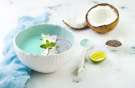 Vegan blue spirulina smoothie and chia pudding bowl topped with coconut flakes and lime zest Reklamní fotografie