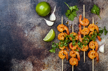 Grilled spicy lime shrimp skewers with creamy avocado garlic cilantro sauce. Top view, overhead, flat lay, copy space