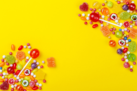 Different types of candies on yellow background, copy space Stock fotó