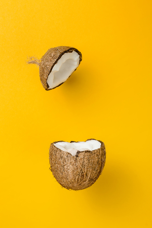 Coconut on yellow colored background, minimal flat lay style
